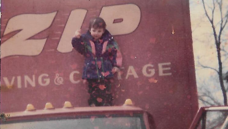 vintage scanned photo of child on top of a-zip moving truck